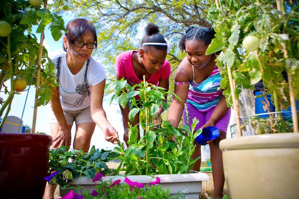 frida teaching children gardening techniques